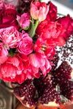Ein Blumenstrauß von roten und rosa Rosen, von Pfingstrosen mit Trauben und von Granatapfelnahaufnahme Stockfoto