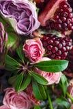 Ein Blumenstrauß von roten und rosa Rosen, von Pfingstrosen mit Trauben und von Granatapfelnahaufnahme Lizenzfreie Stockbilder