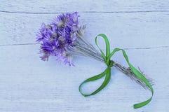 Ein Blumenstrauß von Trockenblumen auf einem hellen hölzernen Hintergrund Lizenzfreie Stockfotos