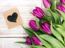 Ein Blumenstrauß von Tulpen und von dekorativer Karte mit Herzen Stockbilder