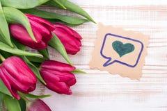 Ein Blumenstrauß von Tulpen und von dekorativer Karte mit Herzen Stockbild