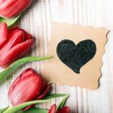 Ein Blumenstrauß von Tulpen und von dekorativer Karte mit Herzen Stockfotografie