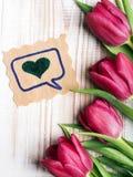 Ein Blumenstrauß von Tulpen und von dekorativer Karte mit Herzen auf einem hölzernen Hintergrund Stockbilder