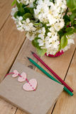 Ein Blumenstrauß von weißen Frühlingsblumen und von altem Weinlesenotizbuch Stockfotografie