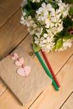 Ein Blumenstrauß von weißen Frühlingsblumen und von altem Weinlesenotizbuch Stockbild