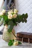 Ein Blumenstrauß von weißen Rosen mit Niederlassungen des Eukalyptus und der Palme Schmuckschatulle mit einer weißen Perlenhalske Lizenzfreie Stockfotos