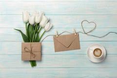 Ein Blumenstrauß von weißen Tulpen, von Tasse Kaffee mit einer Liebesanmerkung und von Umschlag auf einem Herz-förmigen Seil und  stockbild