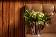 Ein Blumenstrauß von wilden Maiglöckchen in einer alten Teekanne auf hölzernem Hintergrund Stockbild