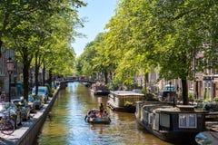 Ein Boot auf der historischen Kanalmitte von Amsterdam Stockbilder