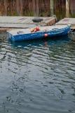 Ein Boot auf einem verwitterten Dock Stockbild