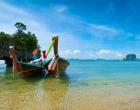 Ein Boot des langen Hecks durch den Strand in Thailand Lizenzfreies Stockfoto