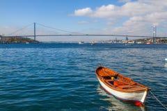 Ein Boot im Bosphorus mit der Brücke im Hintergrund stockfoto
