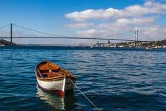 Ein Boot im Bosphorus mit der Brücke im Hintergrund stockfotos