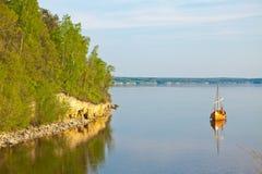 Ein Boot macht ruhige Flussbucht fest Stockbild