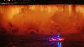 Ein Boot mit Touristen schwimmt am Fuß von Niagara Falls Glättend, wird der Wasserfall durch Flutlichter erneuert stock footage