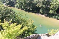 Ein Boot schwimmt auf einen Gebirgsfluss eine Draufsicht von einem Berg lizenzfreie stockbilder