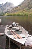 Ein Boot steht im Wasser an einem schönen See an einem Falltag still stockbild