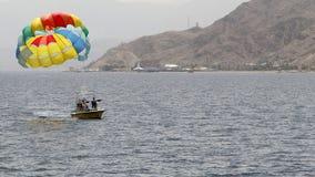 Ein Boot zieht buntes Para-Segeln in dem blauen Meer Elat 2017 Lizenzfreies Stockfoto