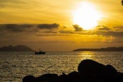 Ein Bootssegeln durch ruhiges Wasser während des Sonnenuntergangs lizenzfreies stockfoto