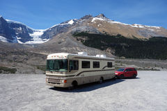 Ein Bounder und ein Schlauchboot parkten mit Rocky Mountains im Hintergrund Lizenzfreies Stockbild