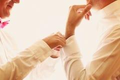 Ein Bräutigam, der auf Manschettenknöpfe sich setzt Stockfoto