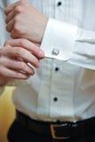 Ein Bräutigam, der auf Manschettenknöpfe sich setzt, wie er angekleidet erhält Stockfoto
