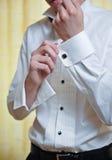 Ein Bräutigam, der auf Manschettenknöpfe sich setzt, wie er angekleidet erhält Lizenzfreie Stockbilder