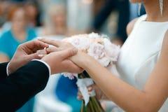 Ein Bräutigam setzt einen Ehering auf den Braut ` s Finger Lizenzfreie Stockfotos