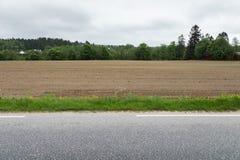 Ein braunes Feld mit gepflogenen Reihen des Schmutzes nahe bei einem Streifen des Grases und der Asphaltstraße Stockfoto