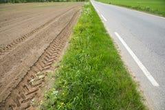 Ein braunes Feld mit gepflogenen Reihen des Schmutzes mit Traktorbahnen, nahe bei Gras und Asphaltstraße Lizenzfreie Stockfotos