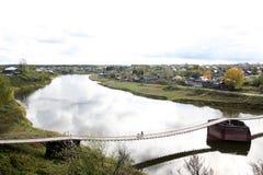 Ein breiter Fluss teilt die Stadt in zwei Teile unter Auf beiden Seiten vom Fluss gibt es Häuser und einen Wald stockbilder