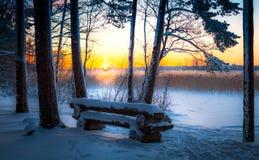 Ein breiter Schneeraum mit einer Holzbank bei Sonnenuntergang Lizenzfreie Stockfotos