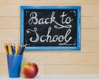 Ein Brett mit einer Aufschriftkreide, zurück zu Schule, ein Glas mit Stockfotos