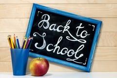 Ein Brett mit einer Aufschriftkreide, zurück zu Schule, ein Glas mit Lizenzfreies Stockfoto