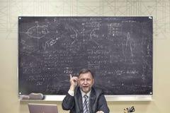 Ein Brett mit mathematischen Beispielen und ein Lehrer am Tisch lizenzfreies stockfoto