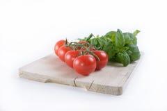 Ein Brett mit Tomate und Basilikum Lizenzfreies Stockbild