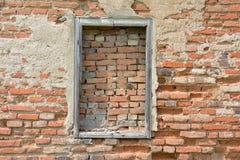Ein bricked Fenster mit Holzrahmen auf der Wand des roten Backsteins stockfotografie