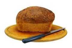 Ein Brotlaib, Messer und ein Brot-Brett Stockbilder