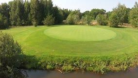 Ein Brummen fliegt über einen grünen Golfplatz mit See