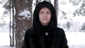 Ein Brunette in einem Pelzmantel steht in einem Wald oder in einem Park an einem schneebedeckten Tag und an den Blicken des Winte stock video
