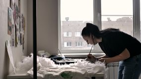 Ein Brunette in einem schwarzen T-Shirt und in den Jeans zeichnet stock video