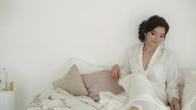 Ein Brunettemädchen in einem Hausmantel sitzt auf dem Bett Photosession der Braut stock video footage