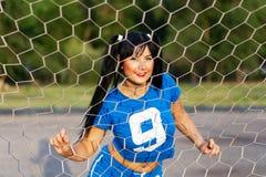 Ein Brunettemädchen in einer Sportuniform steht hinter einem Fußball gat stockbild