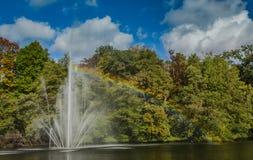 Ein Brunnen in einem Teich, mit einem Regenbogen Stockbilder