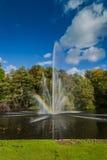 Ein Brunnen in einem Teich, mit einem Regenbogen Lizenzfreie Stockbilder
