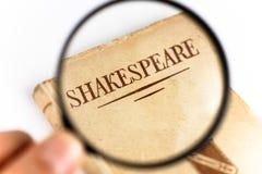 Ein Buch durch Shakespeare unter einer Lupe Lizenzfreie Stockfotografie