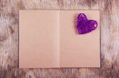Ein Buch mit Leerseiten und einem hölzernen Hintergrund des Weidenherzens Violettes Herz der Niederlassungen und des Tagebuchs Stockfotografie