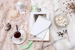 Ein Buch, ein Notizbuch, eine Kerze in einem Glaskerzenständer, parvarda, Erdnüsse im Zucker, eine Statuette eines Engels gemacht stockfotografie