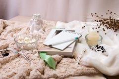 Ein Buch, ein Notizbuch, eine Kerze in einem Glaskerzenständer, parvarda, Erdnüsse im Zucker, eine Statuette eines Engels gemacht lizenzfreie stockfotos