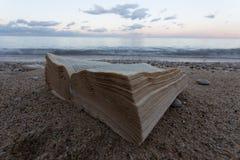 Ein Buch und gelebt in einem verlassenen Strand im Hintergrund ein Strand Stockfoto